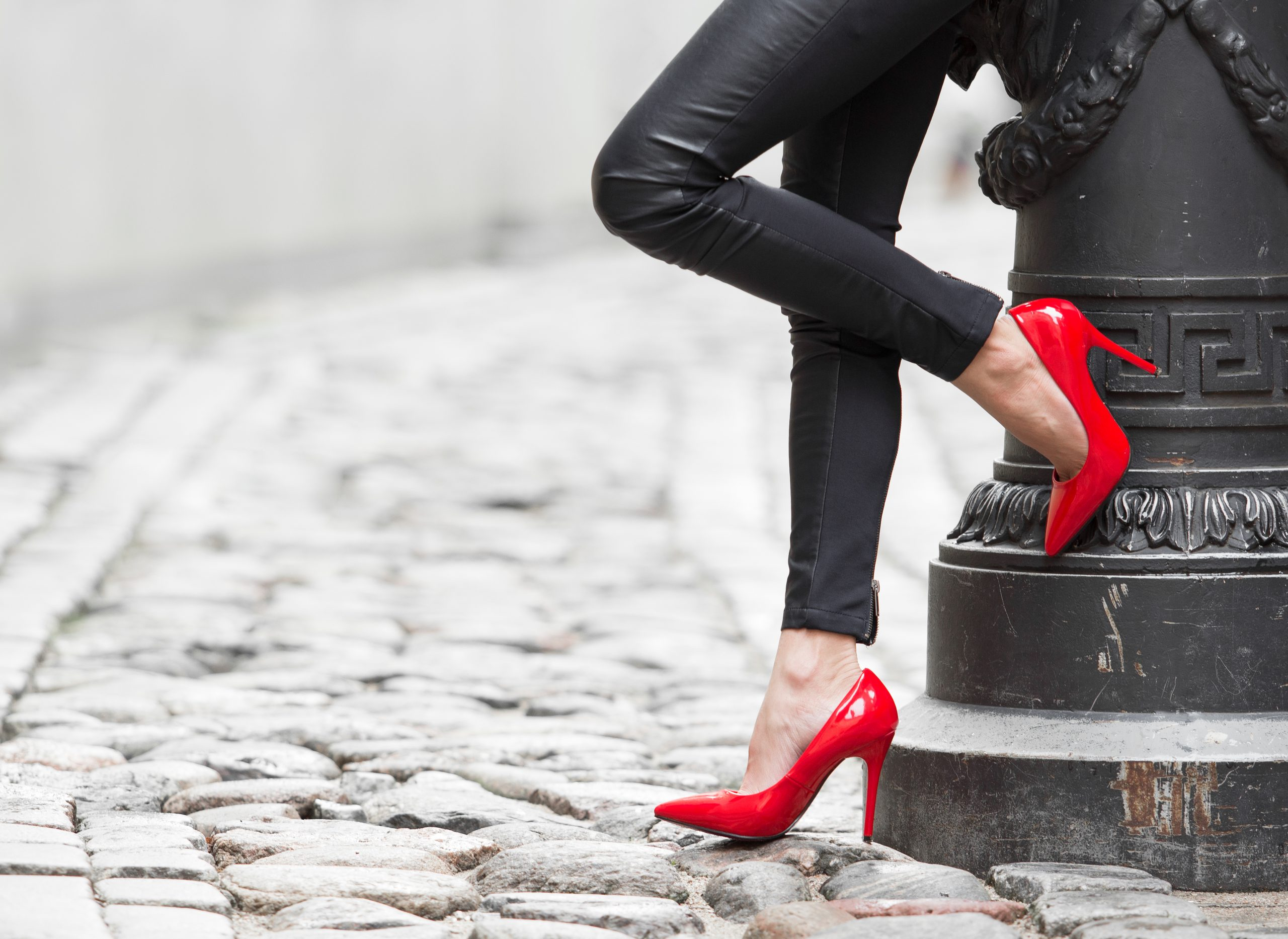 women in red heels leaning up against wall