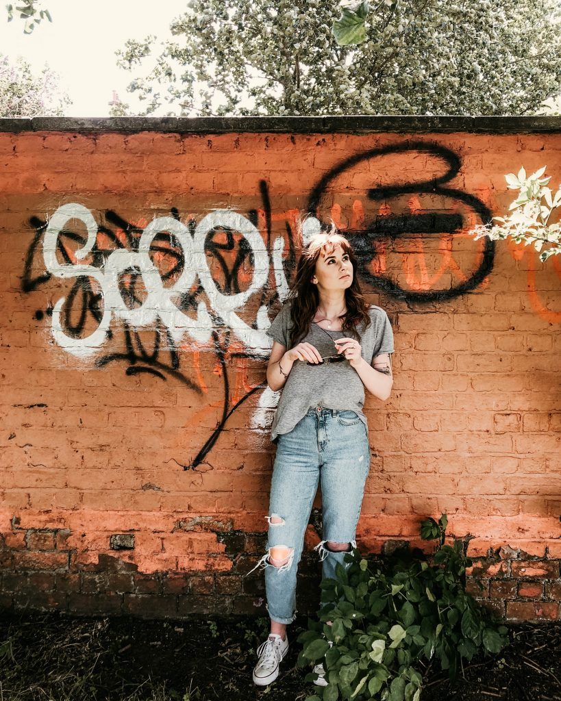 Girl stood in front of a wall that say sorry on it