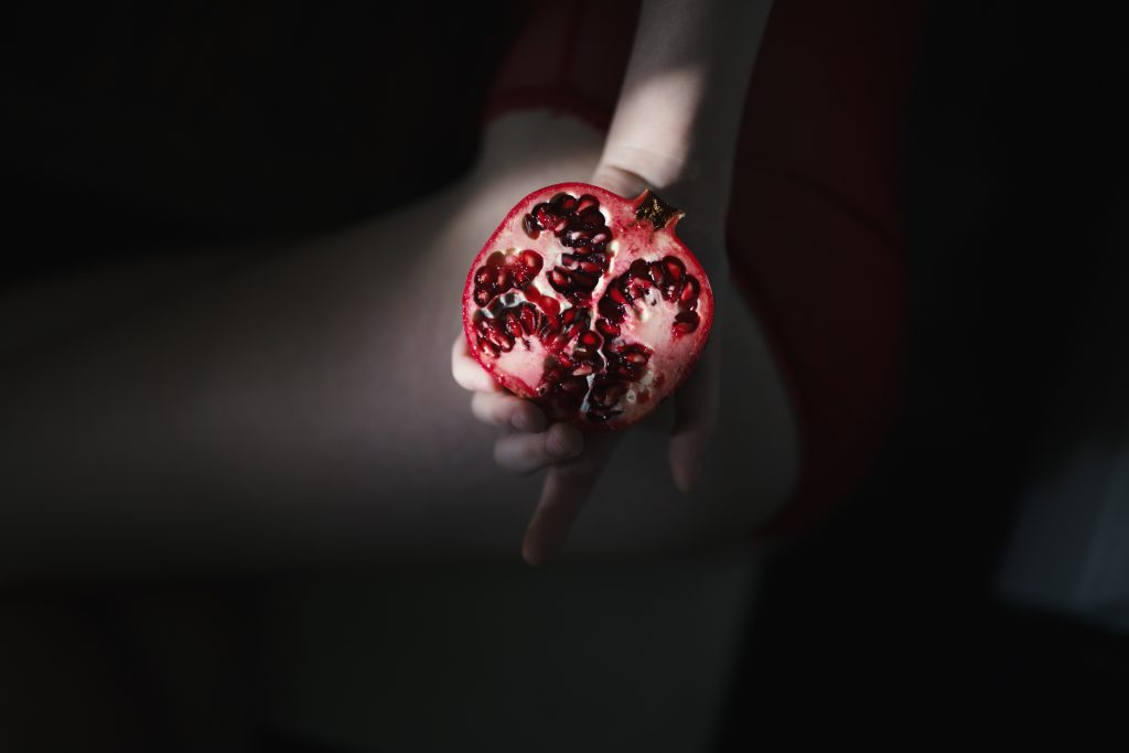 person holding a pomegranate