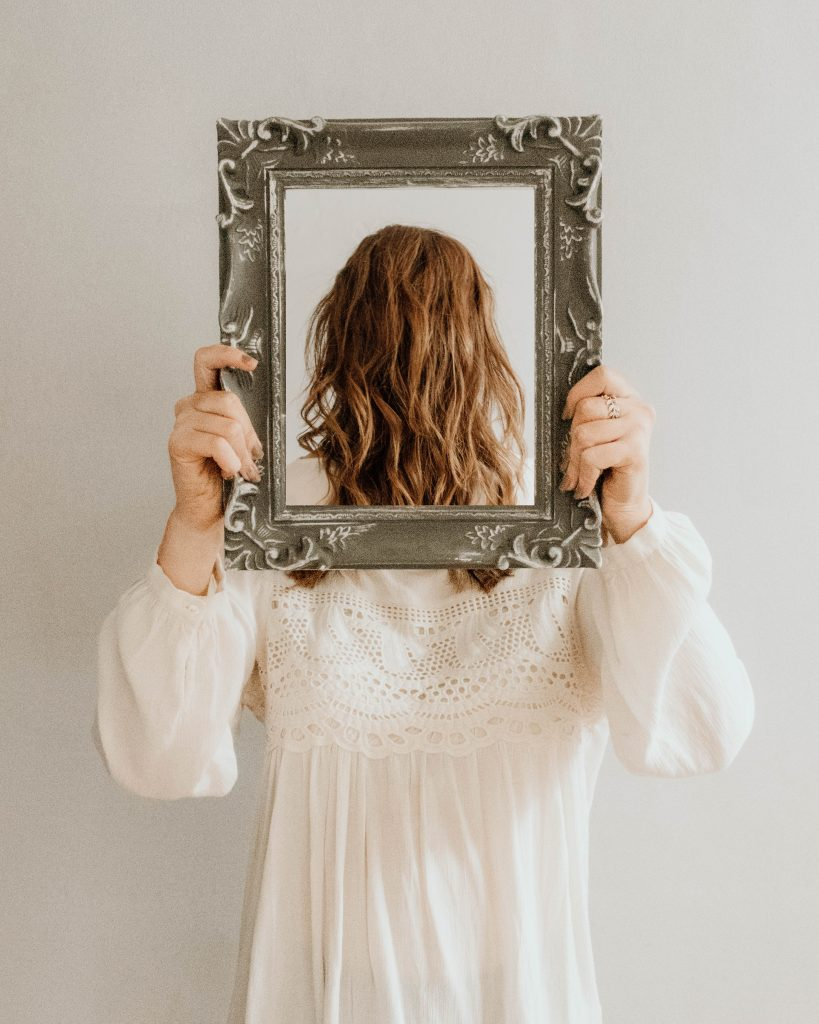 woman holding mirror and looking backwards
