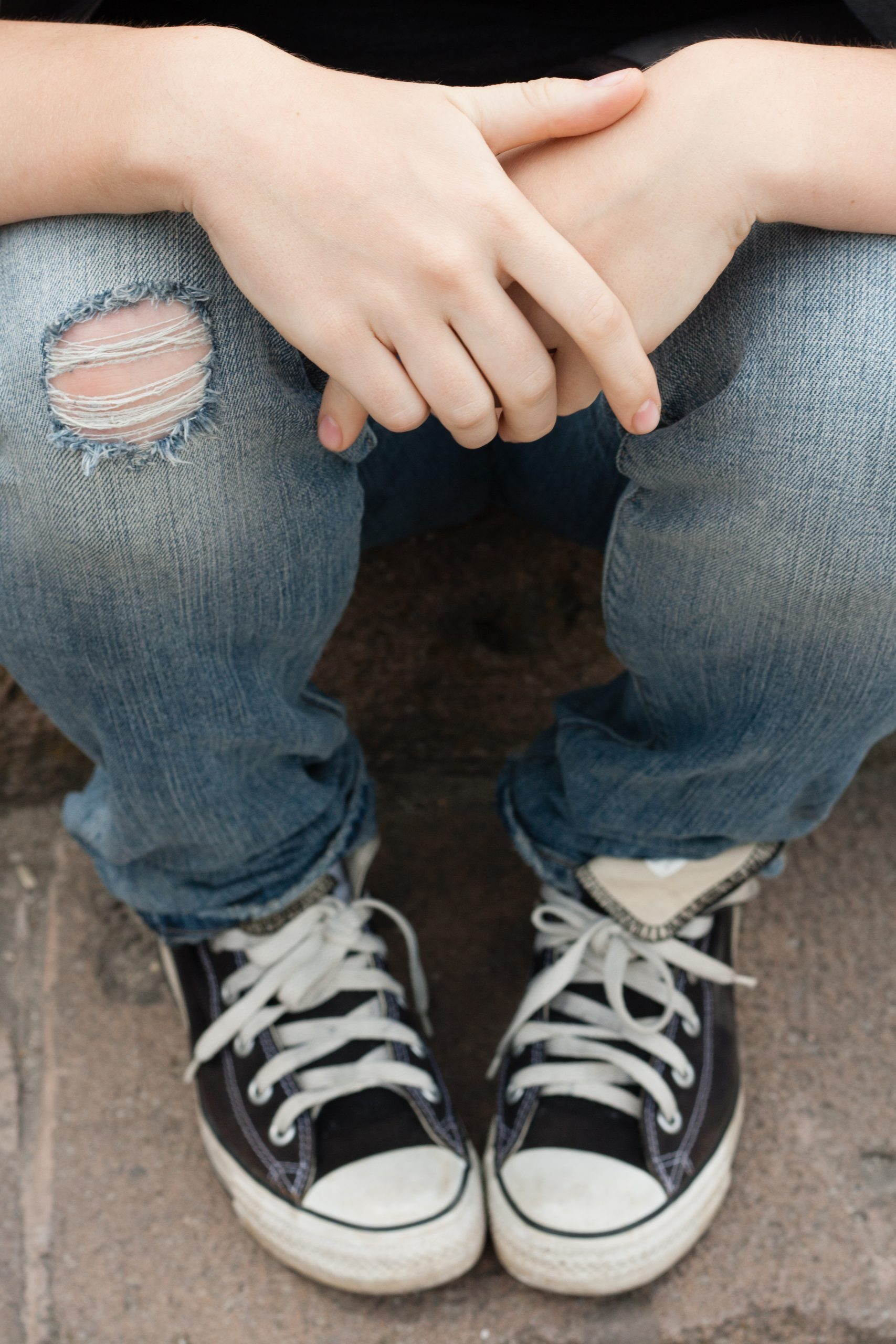 Teen with jeans and converse trainer in an article about teen happiness